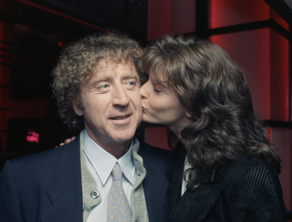 "Actor Gene Wilder, left, gets a kiss from co-star Joan Severance during a premiere benefit for their new movie ""See No Evil, Hear No Evil"" Wednesday, May 11, 1989, New York. The benefit was held for the New York League for the Hard of Hearing. (AP Photo/Ron Frehm)"